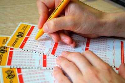 Мужчина заполняет лотерейные билеты