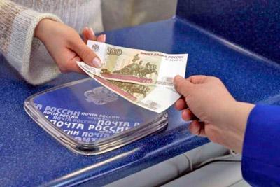 Женщина получает деньги на почте