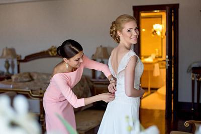Свидетельница помогает одеваться невесте